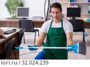 Купить «Young handsome contractor cleaning the office», фото № 32024239, снято 9 мая 2019 г. (c) Elnur / Фотобанк Лори