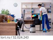 Купить «Young handsome contractor cleaning the office», фото № 32024243, снято 9 мая 2019 г. (c) Elnur / Фотобанк Лори