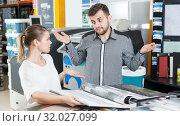 Купить «Couple looking samples of wallpaper in household store», фото № 32027099, снято 17 мая 2018 г. (c) Яков Филимонов / Фотобанк Лори
