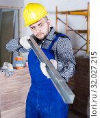 Купить «Professional constructor in helmet is looking at the level of the profile», фото № 32027215, снято 3 июня 2017 г. (c) Яков Филимонов / Фотобанк Лори