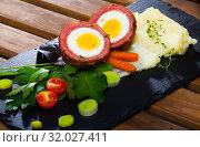 Купить «Scotch egg srved with mashed potatoes and greens, Scottish traditional dish», фото № 32027411, снято 19 августа 2019 г. (c) Яков Филимонов / Фотобанк Лори