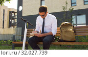 Купить «businessman writing to notebook sitting on bench», видеоролик № 32027739, снято 5 августа 2019 г. (c) Syda Productions / Фотобанк Лори