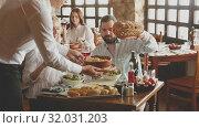 Купить «Male waiter carrying order for visitors in country restaurant», видеоролик № 32031203, снято 26 апреля 2019 г. (c) Яков Филимонов / Фотобанк Лори