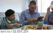 Купить «Modern young family absorbedly looking at smartphones in home interior», видеоролик № 32031251, снято 12 июня 2019 г. (c) Яков Филимонов / Фотобанк Лори