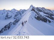 Mountaineers along the snowy south-east ridge of Aletschhorn with Dreieckhorn in background, Bernese Alps, canton of Valais, Switzerland. Редакционное фото, фотограф Clickalps SRLs / age Fotostock / Фотобанк Лори