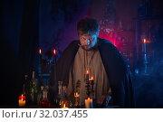 Купить «portrait of wizard with burning candles and magic potions», фото № 32037455, снято 14 августа 2019 г. (c) Майя Крученкова / Фотобанк Лори