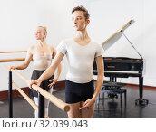Купить «Choreographer woman and young man do exercises at ballet bar in hall with mirror», фото № 32039043, снято 26 апреля 2019 г. (c) Яков Филимонов / Фотобанк Лори