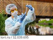 Female ecologist or epidemiologist checks water quality in urban pond. Стоковое фото, фотограф Евгений Харитонов / Фотобанк Лори