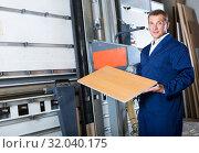 Купить «man cutting plywood with electric saw», фото № 32040175, снято 20 августа 2019 г. (c) Яков Филимонов / Фотобанк Лори