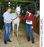 Купить «Portrait of couple standing at stable», фото № 32040243, снято 26 ноября 2018 г. (c) Яков Филимонов / Фотобанк Лори