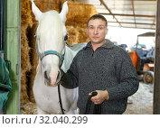Купить «Man in casual clothes who works at stable», фото № 32040299, снято 26 ноября 2018 г. (c) Яков Филимонов / Фотобанк Лори