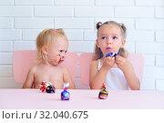 Купить «Две маленькие девочки едят конфеты», фото № 32040675, снято 20 июля 2019 г. (c) Арестов Андрей Павлович / Фотобанк Лори