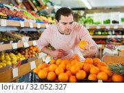 Купить «Man customer choosing fresh oranges on the supermarket», фото № 32052327, снято 27 апреля 2019 г. (c) Яков Филимонов / Фотобанк Лори