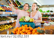 Купить «Positive family couple standing with full cart after shopping and pointing to shelves in fruit store», фото № 32052331, снято 27 апреля 2019 г. (c) Яков Филимонов / Фотобанк Лори