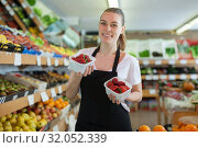 Young woman seller standing with small boxes of strawberry. Стоковое фото, фотограф Яков Филимонов / Фотобанк Лори