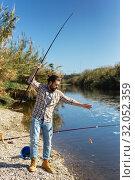 Купить «Adult man standing near river and pulling fish expressing emotions of dedication», фото № 32052359, снято 15 марта 2019 г. (c) Яков Филимонов / Фотобанк Лори