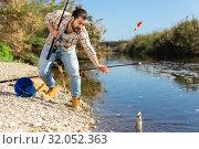 Купить «Adult man standing near river and pulling fish expressing emotions of dedication», фото № 32052363, снято 15 марта 2019 г. (c) Яков Филимонов / Фотобанк Лори