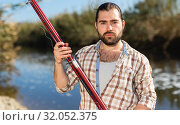 Adult man standing outdoors with angling rod planning to fishing. Стоковое фото, фотограф Яков Филимонов / Фотобанк Лори