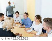 Купить «Group of smiling students brainstorming in classroom», фото № 32052523, снято 5 октября 2017 г. (c) Яков Филимонов / Фотобанк Лори