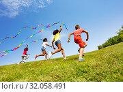Купить «Children run colorful ribbons in park together», фото № 32058491, снято 15 июня 2019 г. (c) Сергей Новиков / Фотобанк Лори