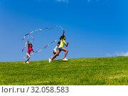 Купить «Three children run fast waving with color ribbons», фото № 32058583, снято 15 июня 2019 г. (c) Сергей Новиков / Фотобанк Лори