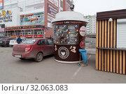 Круглый киоск по продаже кофе на фоне универмага Комсомольский в Красноярске (2019 год). Стоковое фото, фотограф Светлана Попова / Фотобанк Лори