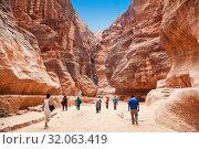 Купить «Tourists in narrow passage of rocks of Petra canyon in Jordan. Petra has been a UNESCO World Heritage Site since 1985. Way through Siq gorge to stone city Petra», фото № 32063419, снято 18 апреля 2012 г. (c) Наталья Волкова / Фотобанк Лори