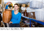 Купить «young woman consumer holding wicker barrel in decor items store», фото № 32063787, снято 13 декабря 2017 г. (c) Яков Филимонов / Фотобанк Лори