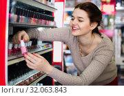 Купить «Smiling woman customer deciding on nail polish», фото № 32063843, снято 21 февраля 2017 г. (c) Яков Филимонов / Фотобанк Лори