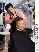 Купить «Young male hairdresser making hairstyle for woman», фото № 32063943, снято 11 августа 2017 г. (c) Яков Филимонов / Фотобанк Лори
