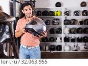 Купить «Happy man is choosing new helmet for motorbike», фото № 32063955, снято 1 сентября 2017 г. (c) Яков Филимонов / Фотобанк Лори