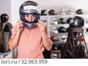 Купить «Adult man is trying up new helmet for motorbike», фото № 32063959, снято 1 сентября 2017 г. (c) Яков Филимонов / Фотобанк Лори