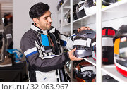 Купить «Man in moto jacket is choosing new helmet for motorbike in the store.», фото № 32063967, снято 1 сентября 2017 г. (c) Яков Филимонов / Фотобанк Лори