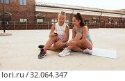 Купить «sporty women or friends with smartphone on rooftop», видеоролик № 32064347, снято 4 августа 2019 г. (c) Syda Productions / Фотобанк Лори