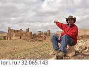 Man sitting in front of the Ksar of Tamedakhte, Ounila River valley, Ouarzazate Province, region of Draa-Tafilalet, Morocco, North West Africa. (2019 год). Редакционное фото, фотограф Christian Goupi / age Fotostock / Фотобанк Лори