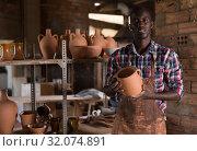 Купить «Craftsman offering ceramic products», фото № 32074891, снято 6 августа 2019 г. (c) Яков Филимонов / Фотобанк Лори