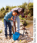 Купить «Man and boy with fish catch», фото № 32074983, снято 26 мая 2019 г. (c) Яков Филимонов / Фотобанк Лори