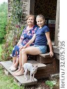 Купить «Aged woman with her granddaughter and sphynx cat sitting on wooden stairs of porch, country house, summer season», фото № 32075735, снято 20 июля 2019 г. (c) Кекяляйнен Андрей / Фотобанк Лори