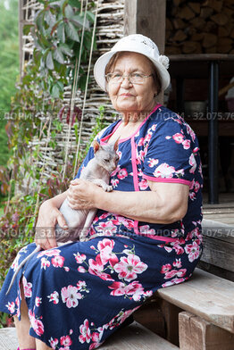 Elderly lady with her sphynx cat portrait, eyeglasses and housecoat, sitting on porch of timber house