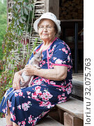 Купить «Elderly lady with her sphynx cat portrait, eyeglasses and housecoat, sitting on porch of timber house», фото № 32075763, снято 20 июля 2019 г. (c) Кекяляйнен Андрей / Фотобанк Лори