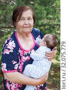 Elderly woman carrying a baby in arms, great grandmother portrait with her great grandchild. Стоковое фото, фотограф Кекяляйнен Андрей / Фотобанк Лори
