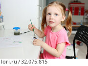 Cute lovely little girl painting with foam brush at home. Стоковое фото, фотограф ivolodina / Фотобанк Лори