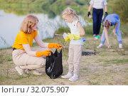 family picks up trash on the beach in summer. Стоковое фото, фотограф Майя Крученкова / Фотобанк Лори