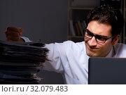Купить «Young businessman working overtime late in office», фото № 32079483, снято 4 октября 2017 г. (c) Elnur / Фотобанк Лори