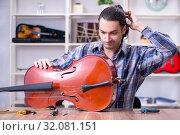 Купить «Young handsome repairman repairing cello», фото № 32081151, снято 4 апреля 2019 г. (c) Elnur / Фотобанк Лори