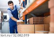 Купить «Sellerman in uniform is calculating bricks», фото № 32082019, снято 26 июля 2017 г. (c) Яков Филимонов / Фотобанк Лори