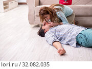Купить «Young couple in first aid concept at home», фото № 32082035, снято 10 мая 2019 г. (c) Elnur / Фотобанк Лори