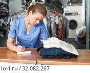 Купить «Female worker writing receipt», фото № 32082267, снято 9 мая 2018 г. (c) Яков Филимонов / Фотобанк Лори