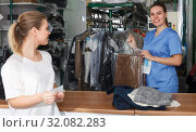 Купить «Glad worker returning clean clothes to customer», фото № 32082283, снято 9 мая 2018 г. (c) Яков Филимонов / Фотобанк Лори