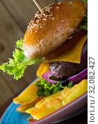 Купить «Cheeseburger with beef, tomato, cheese and lettuce at plate with french fries», фото № 32082427, снято 9 июля 2020 г. (c) Яков Филимонов / Фотобанк Лори